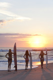 Woman Surfers In Bikinis With Surfboard At Sunset Beach