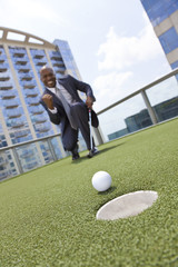 African American Businessman Playing Golf on Skyscraper Rooftop