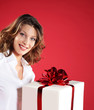 portrait of happy young woman with gift pack, red background