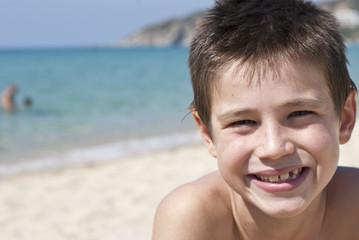 bambino che sorride sulla spiaggia