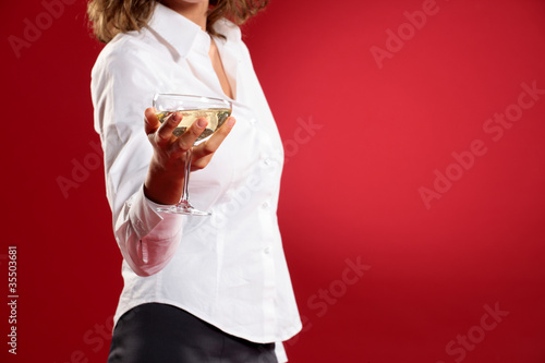 young woman with a glass of champagne on red background