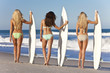 Three Beautiful Women Surfers On Bikinis With Surfboards At Beac