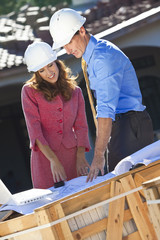 Man & Woman In Hard Hats on Construction Site