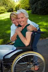 Pflegerin umarmt Seniorin