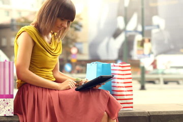 Shopping woman with tablet computer in the city, steadycam shot