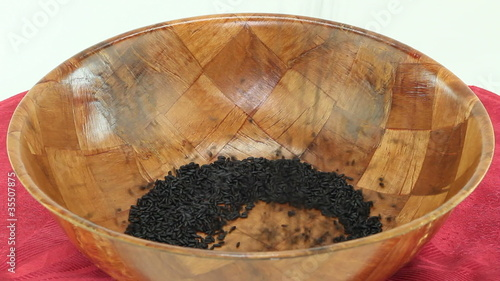 Dry purple black rice falling into a wooden bowl