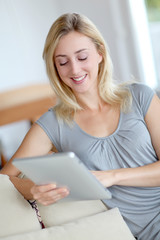 Young woman using electronic tablet in sofa