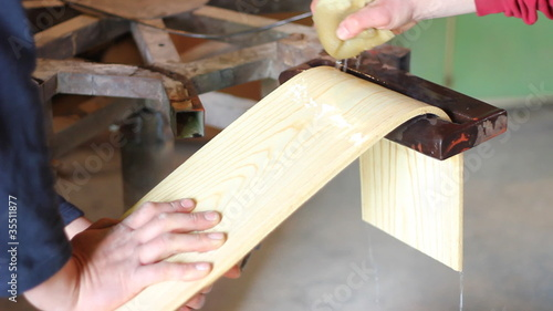 Carpenter bending wooden board