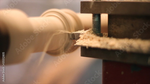 Carpenter scrape a piece of furniture on the lathe