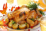 Whole roasted chicken with potatoes and apples on white plate