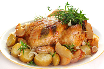 Whole roasted chicken with potatoes and herbs on white plate