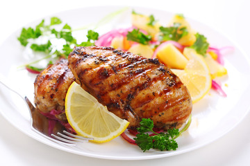 Grilled chicken breast on white plate