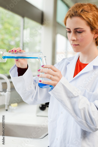 Portrait of a red-haired scientist pouring liquid