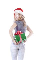 Pretty Santa girl hiding a present gift for New Year