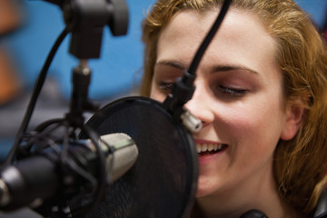 Close up of a young singer recording a track