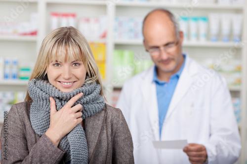 lächelnde kundin mit schal in der apotheke
