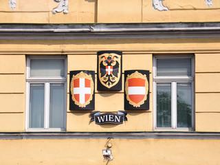 Wappen und Fahne von Wien und Österreich an Fassade in Wien