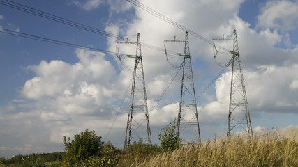 high voltage power pylons on against sky