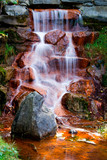 Waterfall Cascading Over Red Algae Covered Rocks