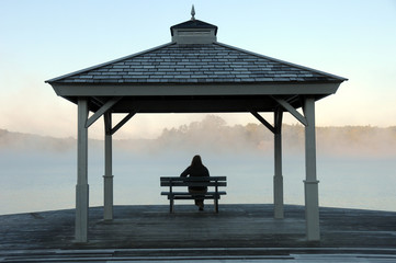 Woman watching sun rise on misty lake under gazebo