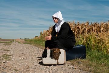 homme déguisé en none assis sur une valise au bord d'un chemin 2