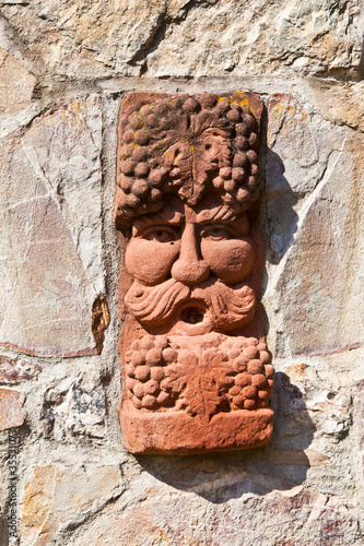 old medieval stone wall with face of baccus, the god of winery