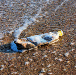 plastic bottle and dust on beach sand