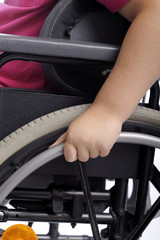 close-up on hand of child in wheelchair