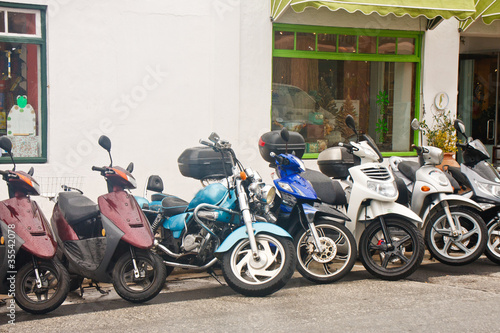 Line of Mopeds in Front of Shops