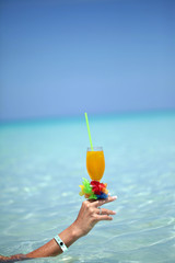 Tropical drink in hand agains the Caribbean Sea