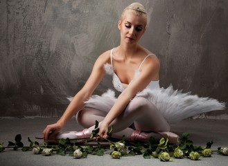 Beautiful ballet dancer with a white roses