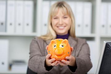 lachende geschäftsfrau mit sparschwein