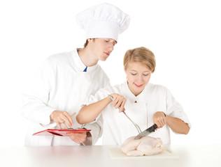 cooks team in white uniforms preparing raw chicken