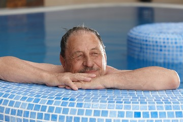 Elderly man relaxing in spa smiling