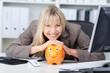 lächelnde geschäftsfrau stützt kopf auf sparschwein