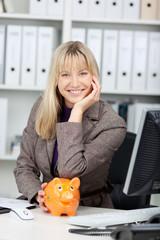 lachende frau im büro stützt sich auf sparschwein