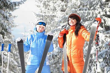 Happy women with skis in the winter landscape