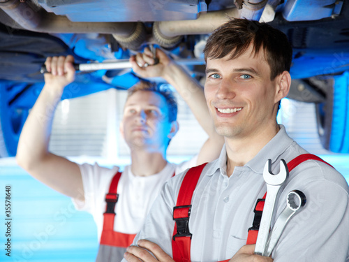 Motor mechanic is satisfied with his job in a garage