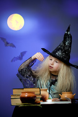 Girl dressed up as witch in night making magic