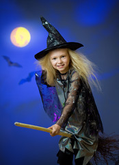Girl dressed up as witch in night flying broom