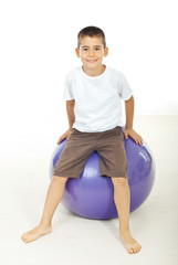 Boy sitting on pilates ball