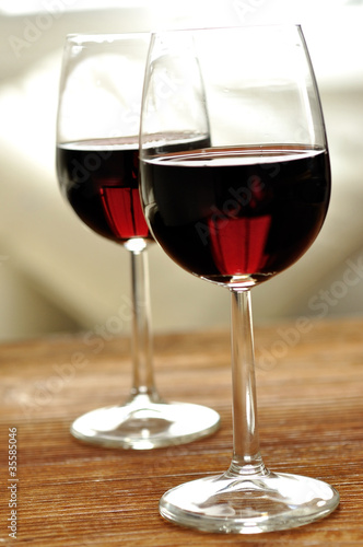Two glass of fine Italian red wine on a table in oak