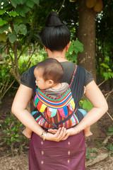 asiatische Frau mit Baby am Rücken