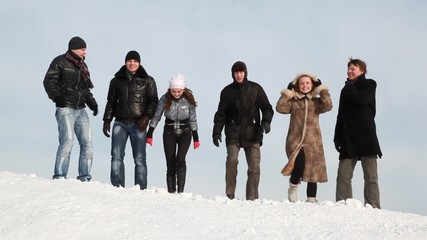 Group of young people are laughing on slope with snow