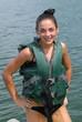Teenage girl wet tubing behind boat wearing life vest