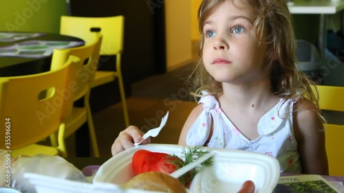 Girl smiling and watches TV while eating at table