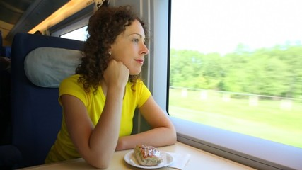 Woman sits in train near window during movement at table