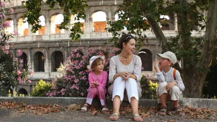 Woman tells story to girl and boy sit in front of Colosseum
