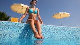 Woman sits on pool border wets feet and tans