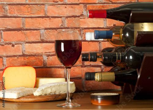 Wine rack , glass of wine and cheese